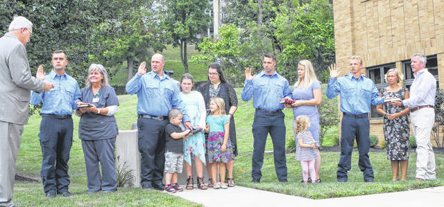 Mayor Mike Barhorst, left, swears in Sidney Fire Department's (SFD) four new firefighters with family members by their side holding The Bible used for taking the Oath of Office. Ross Kohler, from second left to right, and his mother Carol Kohler, of Botkins, stand next to Joshua Waugh, and his wife Brittany and three of his four children, Ben, 3, Bella Homan, 10, and Mia, 5, stand next to Ken Battiston, and his wife Danielle, and their daughter Ernie, 2, and Jared Pleiman, and his parents Mike and Julie Pleiman, of Coldwater, gather out front of SFD's Station 1 on Tuesday afternoon, Sept. 3.