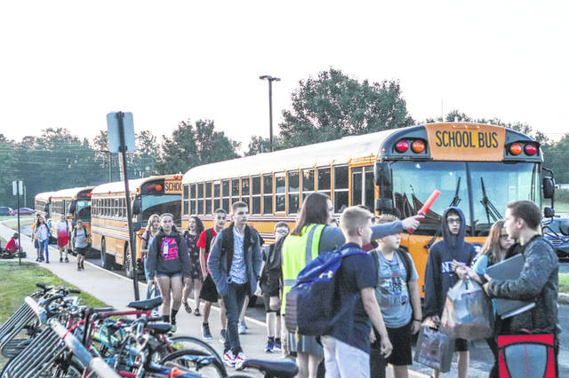 Sidney Middle School students get off the bus Tuesday morning to begin a new school year.