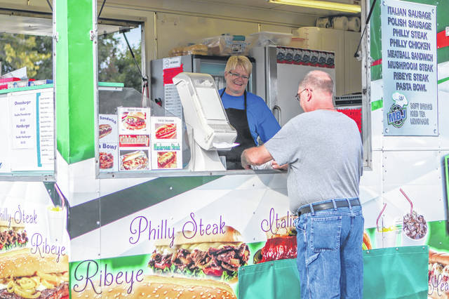 Chris Edwards, of Sidney, gets an Italian sausage sandwich from Jane Jones at her food truck, MBJ Concessions, during the Bicentennial MarketPlace Saturday, Sept. 28, at the Shelby County Fairgrounds.