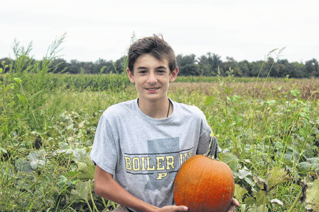 Hunter Lenhart holds one of many pumpkins he grew himself at his family farm in Jackson Center.
