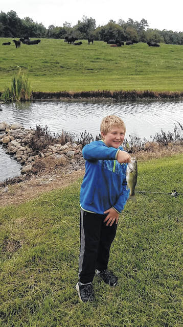Owen Casto displays the fish he caught recently from a pond at the home of Bill and Betty Paulus. He caught the most fish during the event.