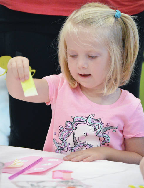 Nora Schulze, 4, of Anna, daughter of Matt and Lisa Schulze, makes a glass of lemonade decoration during Tales for Twos at the Amos Memorial Public Library on Wednesday, Sept. 4. Kids also sang songs and listened to stories. For more information about the library programs, call 937-492-8354.