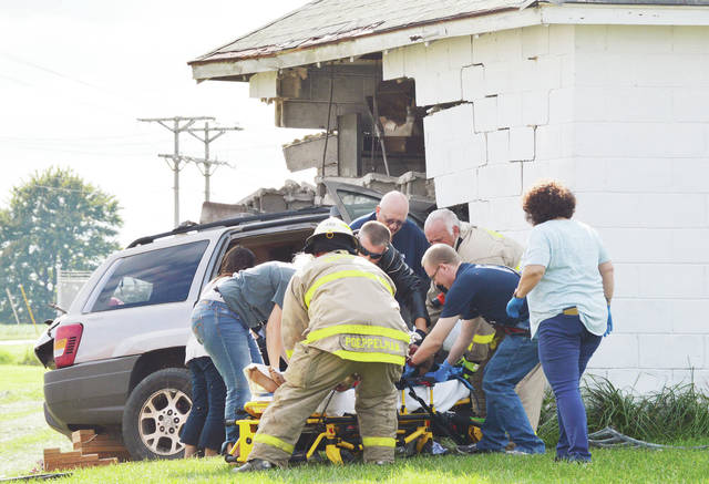 Houston rescue workers set a woman down on a stretcher after removing her from her vehicle which crashed through the cinderblock wall of a detached garage on Wednesday, Sept. 4. The woman was northbound on state route 66 shortly before 5 p.m. when she lost control of her vehicle at the intersection of Russia-Versailles Road. The car left the west side of state route 66 and drove through a field before crashing into the building. Careflight landed in a nearby field to take the woman to a hospital. The Shelby County Sheriff's Office is investigating the single vehicle crash.