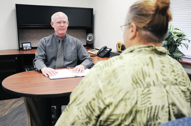New Job and Family Services Director Steve Pulfer, left, talks with Patty Raymond, both of Sidney, in Pulfer's office.