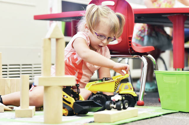 Paizleigh Keller, 4, of Sidney, daughter of Jessie Keller, works with trucks and blocks in the Whittier Early Childhood Center classroom of Lindsay Geuy on Tuesday, Sept. 10. Students were also working with train tracks and a sensory station consisting of a tub filled with beans, scoops and sieves to work with.