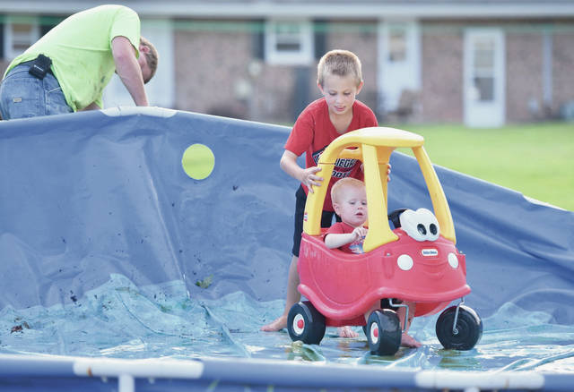 Jerry Ahrns, left to right, takes down the family pool for the year while his sons, Zach Ahrns, 8, and Evan Ahrns, 1, all of Fort Loramie, play on the bottom of the pool on Wednesday, Sept. 11. The brothers are also the children of Melissa Ahrns.
