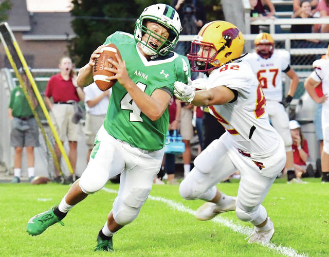 Anna senior quarterback Bart Bixler runs with pressure from New Bremen's Brandon Krauss during a Midwest Athletic Conference game on Friday in Anna. Bixler ran for 64 yards and three touchdowns and threw for 62 yards.