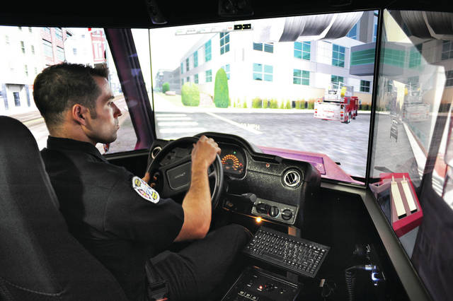 Sidney firefighter Ken Battiston, of Troy, operates a firetruck driving simulator that is held inside the Mobile Driving Simulation Lab that was parked next to the EMA building on Friday, Sept. 13. The elaborate simulator has three large screens and can vibrate.