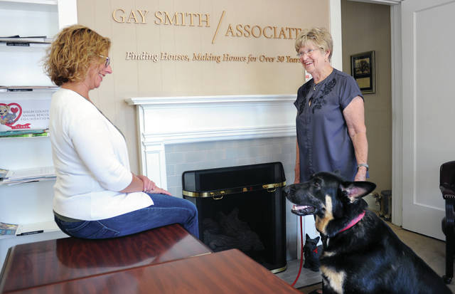 Broker and owner of Gay Smith/Associates Gay Smith, right, talks with her office manager, Lori Shoemaker, both of Sidney, as Smith's dog Trump watches in Smith's office Wednesday, Sept. 18.