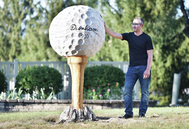 Brad Dunham, of Sidney, displays his giant golf ball on a tee that he constructed in his parents', Mark and Lynne Dunham, yard. The tee he carved from an ash tree that had been growing in the yard until it became infested with the emerald ash borer and died like almost all the ash trees in the area. The tree was not wide enough to make a golf ball so he got some thicker ash tree wood from a friend and carved it into the golf ball before mounting it onto the tee. The golf ball weighs 530 pounds. Dunham used a chainsaw for most of the carving but did some finishing work with a grinder. Dunham chose a golf ball and tee because his father is an avid golfer. A spotlight that had been insalled to illuminate the once healthy ash tree now turns on to light-up the giant sculpture at night.
