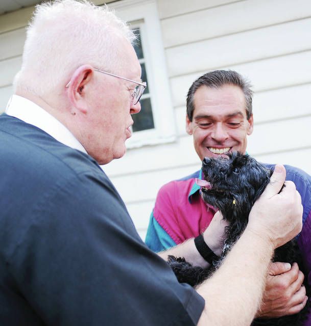 The Rev. Bob Aikins, left, of Englewood, blesses Roy Elder's, of Sidney, service dog named Stephanie Marie, during a blessing of the pets service at St. John's Lutheran Church on Saturday, Sept. 21.