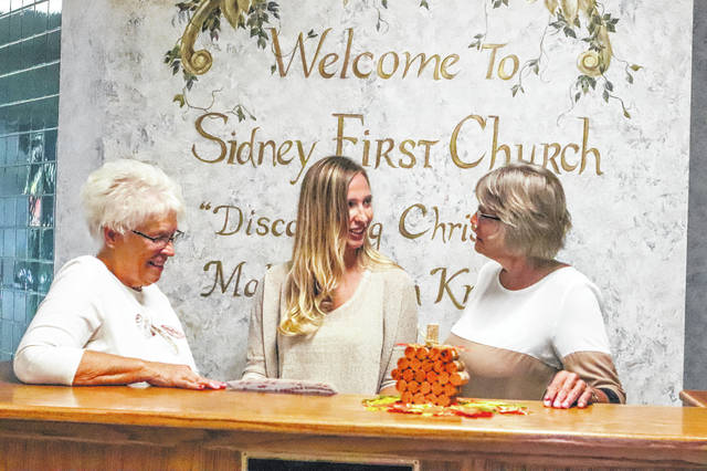 Barri Grandey, chairman of Autumn Leaves Luncheon and Bake Sale,Amber Bucio, co-chairman, and Terri Cooper, Chairman of Apple Dumpling committee, discuss the agenda for the Autumn Leaves event planned for Oct. 8.