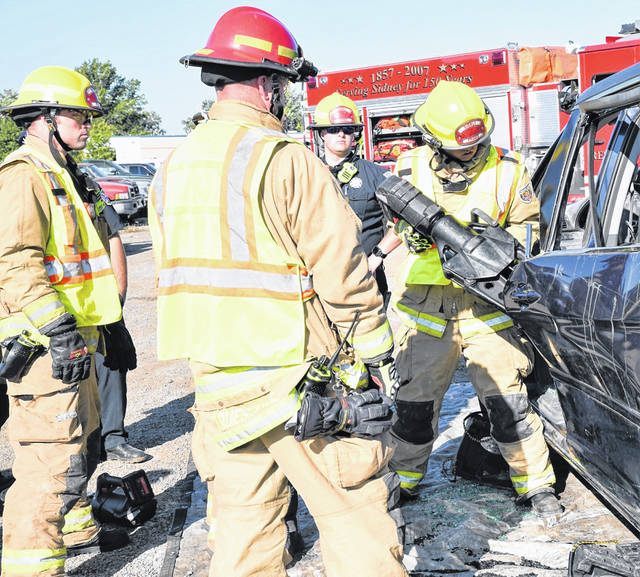 The Sidney Department of Fire & Emergency Services's firefighters Ken Battiston, from left, Lt. Jason Truesdale, Joshua Waugh and Jared Pleiman practice using the Jaws of Life during vehicle extrication training Wednesday morning at Wreckers Towing & Transport on North Stolle Avenue. Truesdale trained the men using a salvaged 2005 Honda Odyssey van donated by State Farm Insurance company.