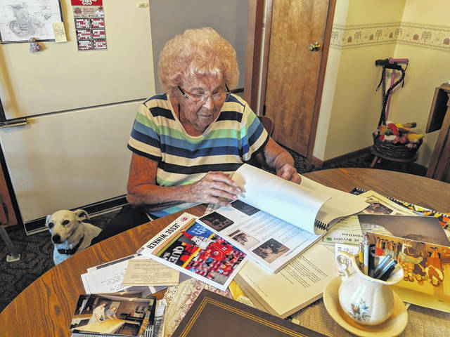 Lucille Meyer looks through some of her memories of the last 100 years while her dog, Tiny, watches her. Meyer will celebrate her 100th birthday on Oct. 16.