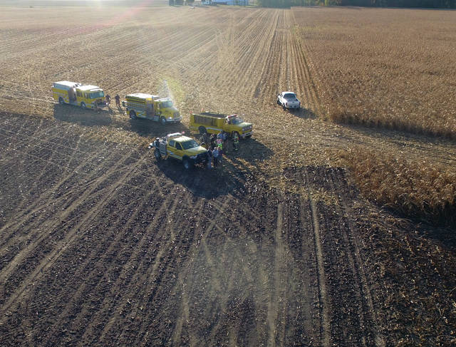Fletcher firefighters make a last check of standing corn and soy beans to make sure that a field fire, which consumed some 60 acres, is fully extinguished Sunday, Oct. 13, around 6 p.m.