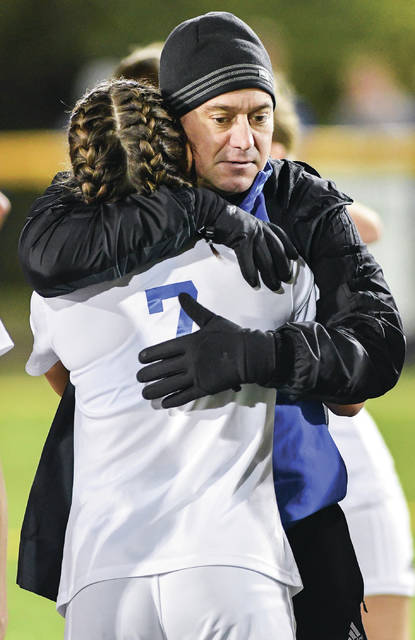 Lehman Catholic coach Jeremy Lorenzo hugs Tori Lachey following the team's 6-1 loss to Cincinnati Country Day in a Division III regional semifinal on Tuesday at Alumni Field in Centerville. It was the final game for Lorenzo, who hugged each player following his postgame address to the team.