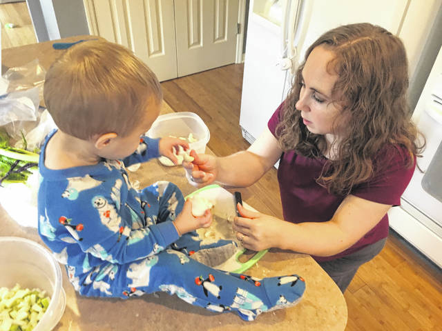 Cara Wolters receives some help from her son, Luke, in preparing a dish for supper.
