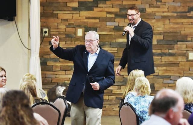 Shelby County Sheriff John Lenhart, left, and auctioneer Justin Vondenhuevel work the room during the Bad Art Ball auction.