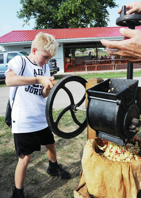 Northwood intermediate student C.J. Goeffena, 10, of Sidney, son of Stacy and Brad Goeffena, works an apple press.