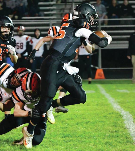 Minster senior quarterback Jacob Niemeyer breaks free from Versailles' Adam Kremer during a Midwest Athletic Conference contest on Friday at Memorial Field in Minster.