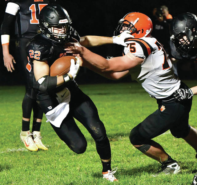 Minster senior running back Alex Schmitmeyer fights off Versailles' Isaac Grilliot during a Midwest Athletic Conference game on Friday at Memorial Field in Minster. The Wildcats host neighboring rival New Bremen this Friday.