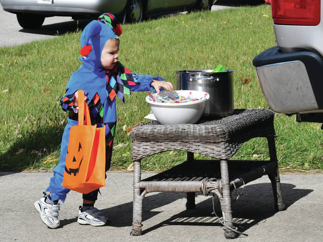 Jackson Fullenkamp, 1, of Troy, son of Adam and Brittany Fullenkamp, looks over his trick or treat options Sunday, Oct. 27 afternoon in Botkins. The Fullenkamps came back to their hometown of Botkins for trick-or-treat with family.