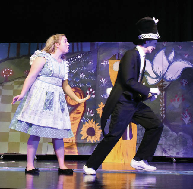 Alice (L) ( played by Callie Lentz) tries to speak to the White Rabbit (Liam McKee) as he runs away.