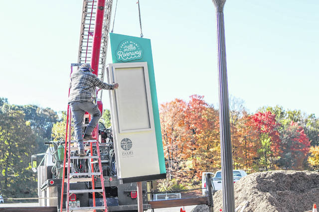 KAPSigns employees Terry Evans (in the truck) and Jim Sizemore, on the ladder, were busy installing a new Great Miami Riverway kiosk by Geib Pavilion at Tawawa Park Friday morning. The city is part of the riverway program which allows people to visit locations along the river via an app on their phone.