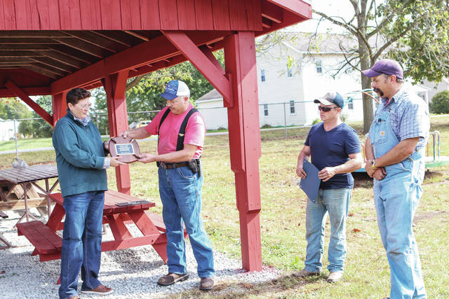 Lockington Mayor Tracy Johnson, left, presents a plaque to the Lockington Volunteer Fire Department for their input in helping the shelter. The rebuilt shelter was partially funded through a $750 Walmart Community Foundation Grant, and the labor was provided by members of the Lockington Volunteer Fire Department. Outdoor tables were donated by Lockington United Methodist Church.