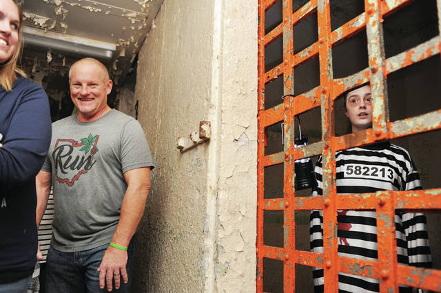 Pyper Sharkins, right, 16, of Troy, daughter of Shari Williams, plays the ghost of Helen Deal inside a cell at the old Sidney jail during the Shelby County Historical Society ghost tour on Wednesday, Oct. 9. Walking past the cell is Tom Martin, of Sidney.