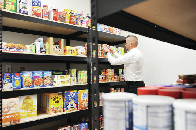 Shelby County Veterans Services Commission Executive Director Chris North, of Sidney, stocks the shelves of the new veterans food pantry Thursday, Oct. 17.