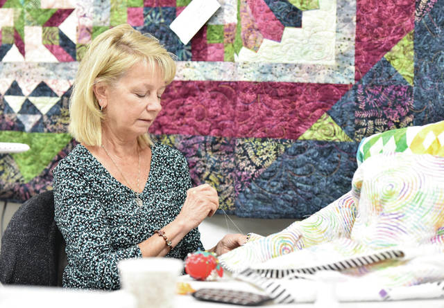 Jeanette Timmerman, of Fort Loramie, works on a quilt during an open sew session at Kari's Custom Quilting near Anna on Thursday, Oct. 17.