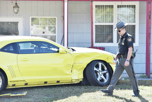 A bright yellow Chevy Camaro, owned by Peter Hasselbeck, of Houston, sits damaged in the front yard of a house on the 5000 block of state route 47 near Houston on Friday, Oct. 18. The Camaro was one of several parked cars with no people in them that were struck by a woman driving a car who was involved in an accident involving a combine.