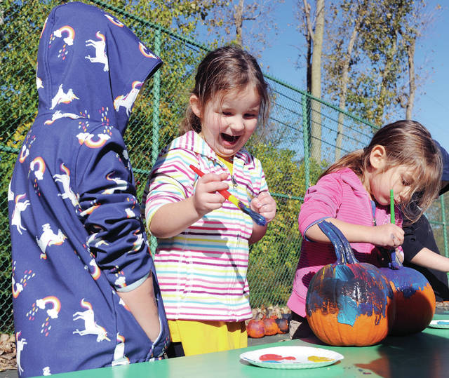 Vayda Ludwig, second from left, 4, of Sidney, daughter of Jeff and Marcia Ludwig, laughs while painting a pumkin during Fall Fun Farm Day at the Sidney-Shelby County YMCA on Wednesday, Oct. 23. Standing next to Vayda are, Caroline Burns, left, 4, daughter of Megan and Nate Burns and Riley Jenkins, 4, both of Sidney, daughter of Christina and Rob Jenkins. Kids also fed alpacas and played in corn.