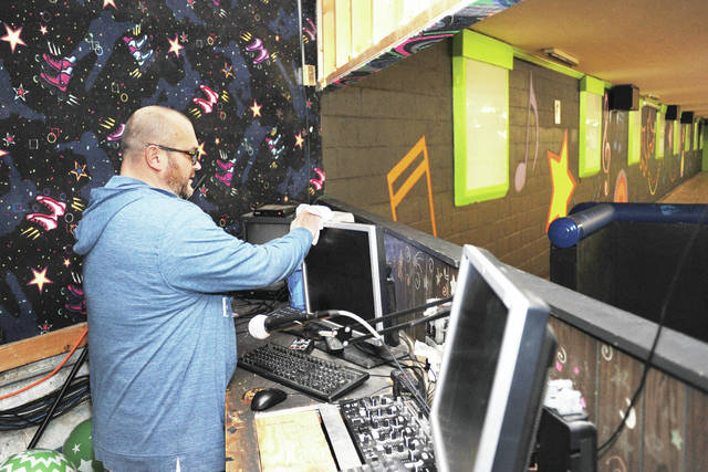 Dan Egbert, of St. Marys, cleans off a computer monitor at the Rolling Hills Skating Rink on Wednesday, Oct. 23. Egbert is the skating rink's new owner.