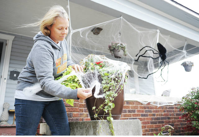 Heather Dunn, of Sidney, covers her porch on Main Avenue in a fake spiderweb to go along with her giant spider for the Halloween season on Tuesday, Oct. 22. A strong wind was threatening to blow the giant spider down.
