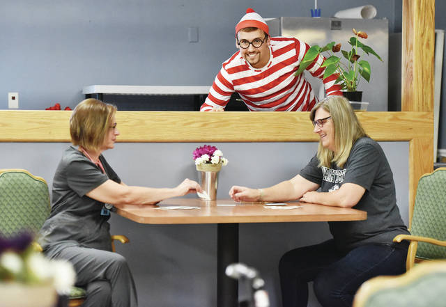 Registered Nurse Beverly Myers, left, and Activities Director Teresa Katterhenry play cards as Sidney Care Center Administrator Ian Cali, of Troy, peeks out over their game while dressed as Waldo from the books Where's Waldo? at the Sidney Care Center on Friday, Oct. 25. Sidney Care Center and the Senior Center of Shelby County are hosting a Where's Waldo game on Wednesday, Oct. 30, from 10 a.m. to 4 p.m. Waldo will pop up in various locations around Sidney. People who see Waldo can take a picture of him and text it to 937-507-2210. The first person to get their photo of Waldo sent at each location wins a prize.