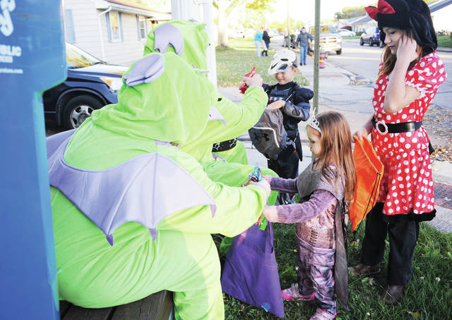 Taylar Stephens, left to right, and Matthew Rittenberry, hand out candy to Hunter Keen, 9, Haley Keen, 11, and Heather Keen, 4, all of Jackson Center, during trick-or-treating in Jackson Center on Sunday, Oct. 27.