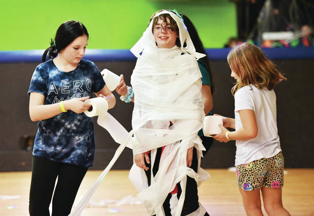 Tayler Douglas, 12, son of Tony and Bridget Douglas, wrapped in toilet paper by Ava Denner, left, 12, daughter of Terra Denner and Kevin Denner, and Abagail Danner, 8, daughter of Brianna Johnson and Josh Danner, all of Sidney, at Rolling Hills Skate on Sunday, Oct. 27 at 1 a.m. during a Halloween themed party.