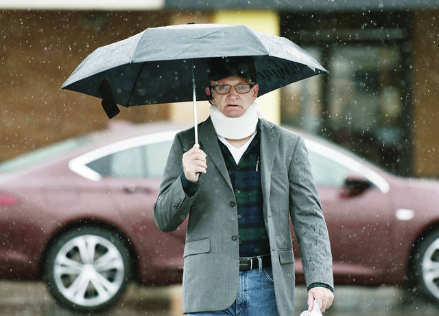 """Maynard Thomas, of Sidney, walks away from Kroger wih an umbrella that says """"hello sunshine"""" on one side of it. Thomas made use of the ironic umbrella on a very rainy Wednesday, Oct. 30."""