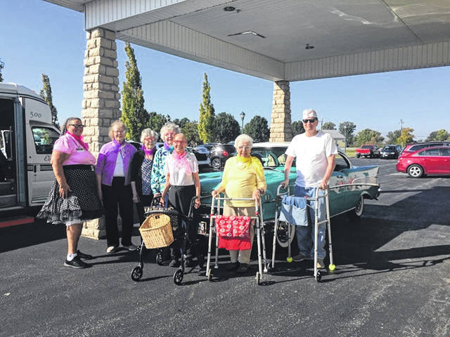 Members of Elmwood Assisted Living of New Bremen stand by a classic car outside of Romer's in Celina. The seniors attended a WCSM event that included music, dancing, food, and root beer floats.