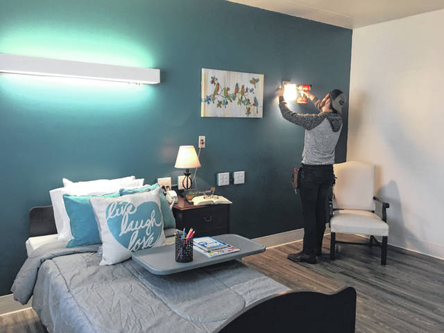 Codey Dillon, assistant plant operations manager, puts the finishing touches on newly remodeled private long-term care suite at Troy Rehabilitation & Healthcare Center.