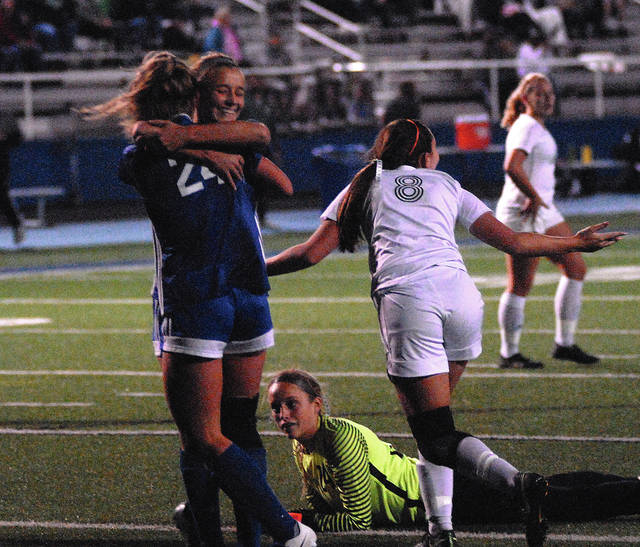 Lehman Catholic's Rylie McIver hugs Noelle Dexter after Dexter's goal as Catholic Central's Natalie Troop and goalie Libby Woeber react during a Division III district final on Thursday in Xenia.