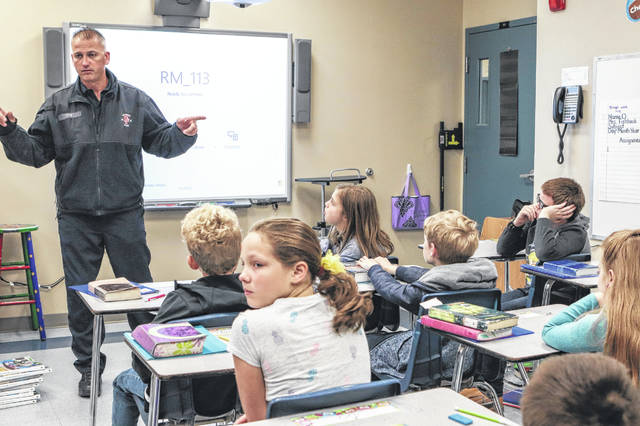Sidney Firefighter Mike Utz talks with Becky Fishback's fifth-grade class at Christian Academy School Monday about fire safety Utz was answering the student's questions about fire safety. The week of Oct. 7 is Fire Safety Week.