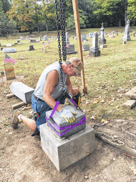 Mark Smith of Gravestone Transformations works to reset the gravestone of two brothers who served in the Civil War in in Graceland Cemetery recently. The process includes leveling and resetting the stone. It will then be cleaned with a biological solution that will kill the algae, fungi, lichen and mold that over time, has caused the stones to darken.