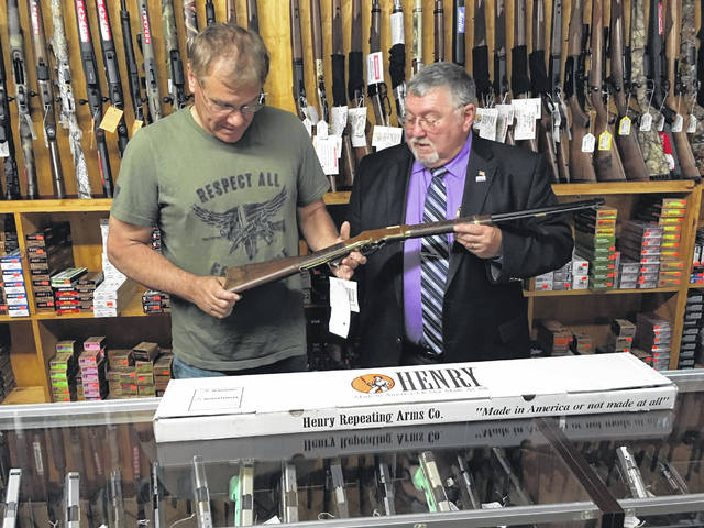 Mark Henman of Tactical Solutions, left, examines the Serial No. 1 Henry Standard Shelby County Commemorative Rifle along with Shelby County Commissioner/ Shelby County Bicentennial Committee Co-Chair Bob Guillozet in preparation for the sale of raffle tickets. The proceeds of the sale of the raffle tickets will be used for the Shelby County Bicentennial celebration.