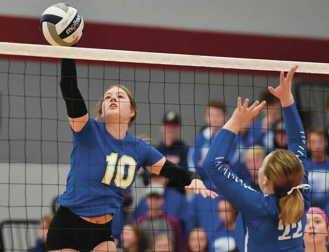 Russia's Ashley Scott spikes as Franklin-Monroe's Matilda Earwood tries to block during a Division IV district final on Saturday at Troy High School's Trojan Activities Center. Scott had a school-record 34 kills in the win.
