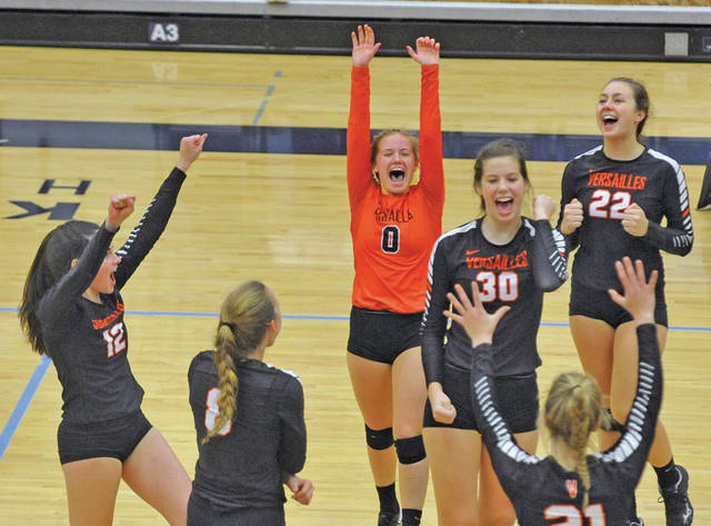 Versailles players celebrate after winning a point late in Thursday's Division III regional semifinal match against Miami East at Fairmont's Trent Arena. The Tigers will face Cincinnati Hills Christian Academy in a regional final on Saturday.
