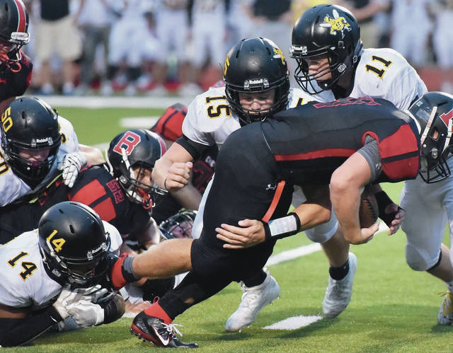 Sidney's Ryan Cagle, center, and Beau Davis bring down Bellefontaine's Garrett Gross during a nonconference game on Sept. 6 at AcuSport Stadium in Bellefontaine. Cagle was named first team all-Southwest district in Division II.
