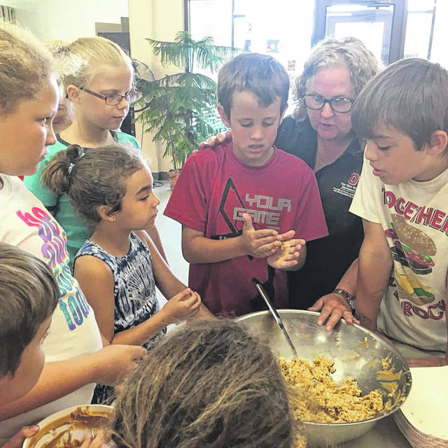 Alpha Community Center provides food and also teaches how to prepare it. A group of kids visit the center and learn how ingredients can be made into cookies.